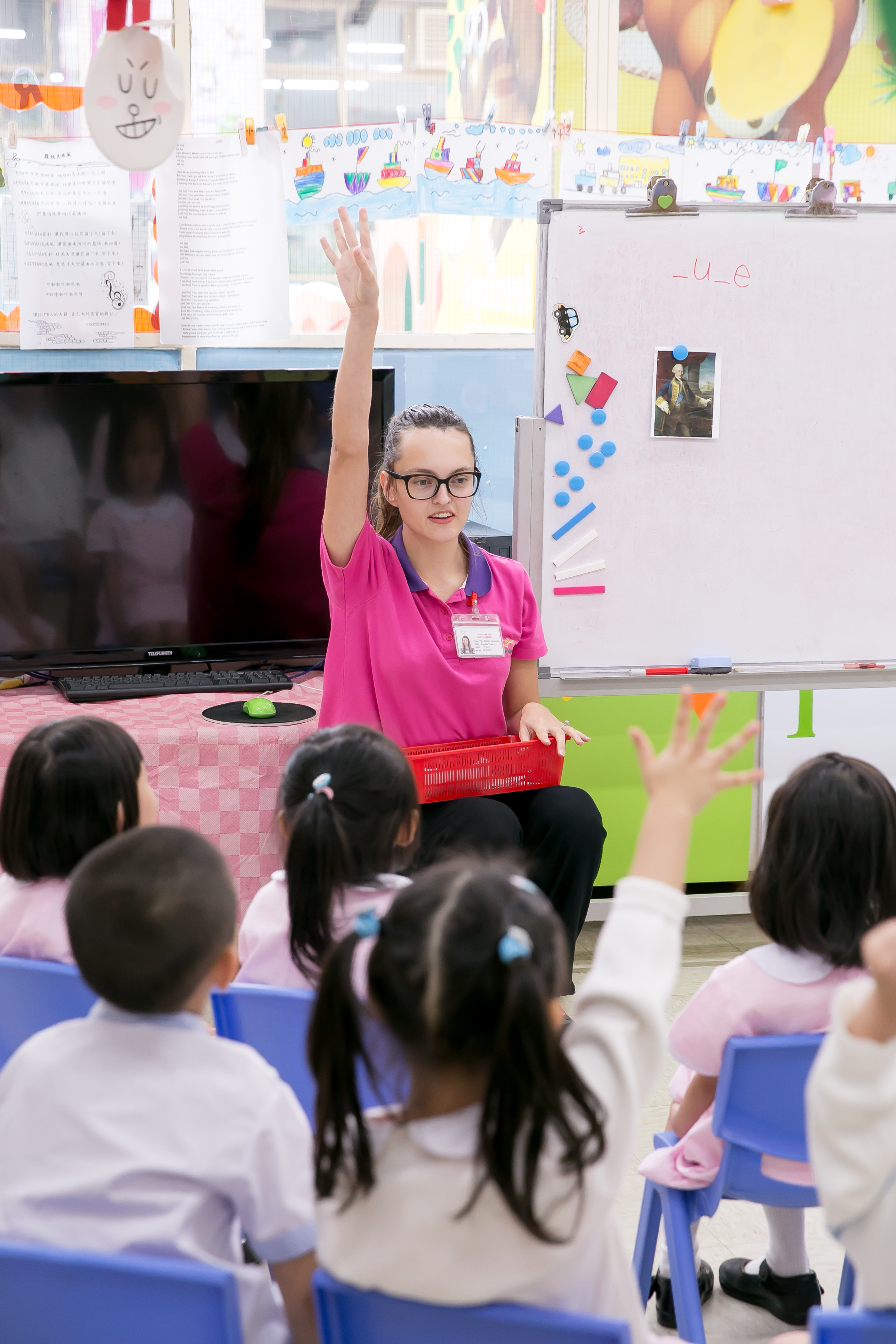 an early career TEFL teacher is sitting in front of a group of asian kindergarteners with her hand raised
