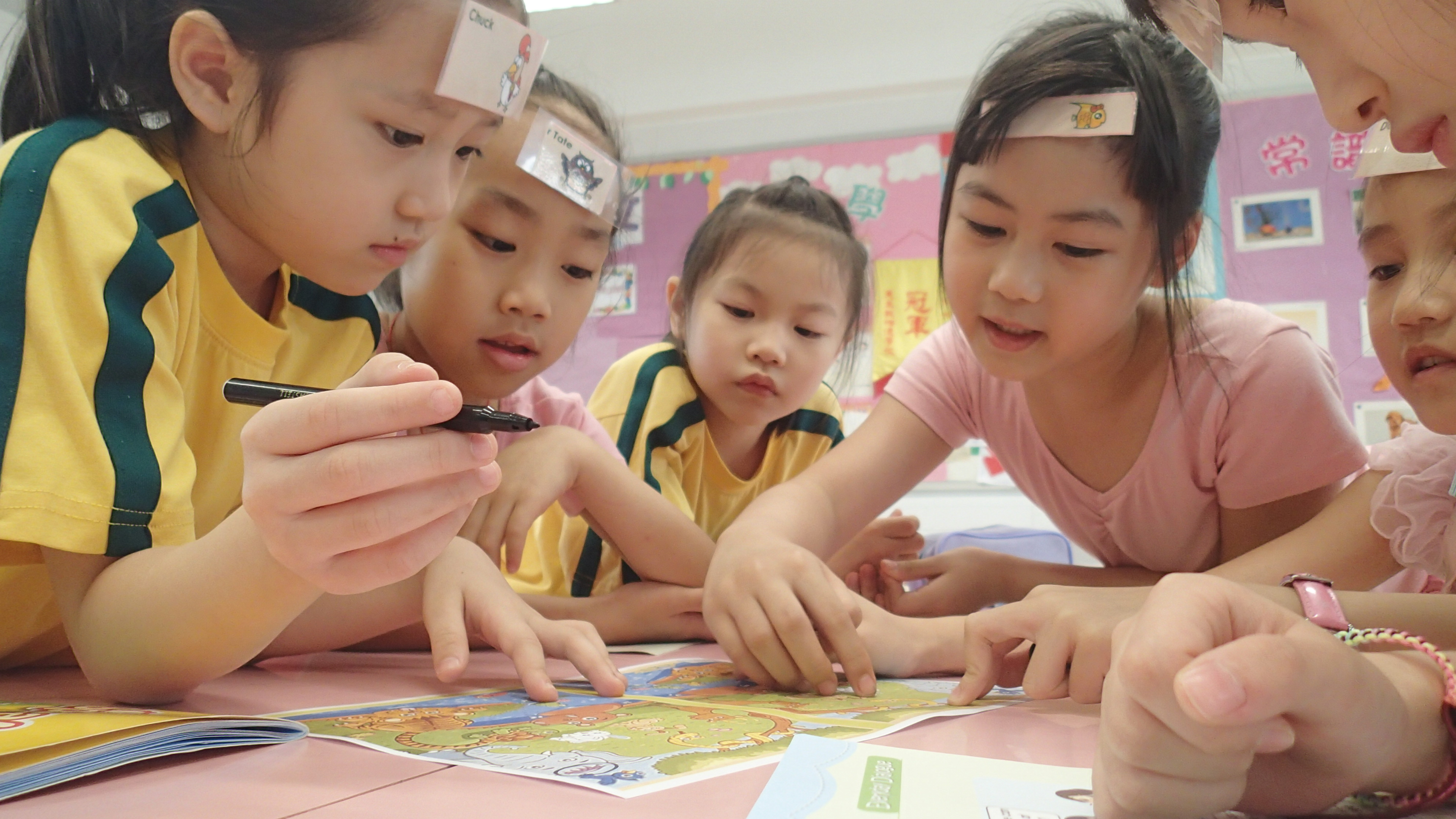 a group of asian girls are playing a table game in a TEFL classroom