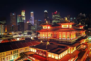 night view on Singapore old chinese building in lights and skyscrapers background