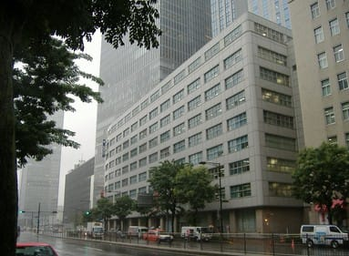 an eight-story building next to a skyscraper in tokyo, japan